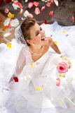 Sposa di risata felice che si siede all'aperto sul pavimento con i petali Immagini Stock Libere da Diritti