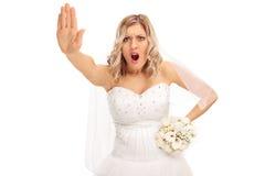 Sposa dispiaciuta che fa un gesto di mano di arresto Fotografie Stock