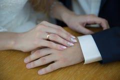 Sposa e groom& x27; mani di s con le fedi nuziali sulla tavola marrone Fotografie Stock