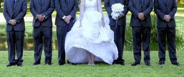 Sposa e 6 Groomsmen allineati all'aperto su erba verde immagini stock libere da diritti