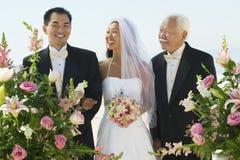 Sposa e padre Looking At Groom immagine stock libera da diritti