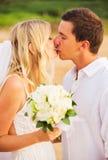 Sposa e sposo, bacianti al tramonto su una bella spiaggia tropicale Fotografia Stock Libera da Diritti