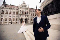 Sposa e sposo che abbracciano nella vecchia via della citt? La coppia di nozze cammina a Budapest vicino alla sede del parlamento immagine stock libera da diritti