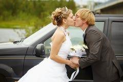 Sposa e sposo che baciano vicino ad un'automobile immagini stock libere da diritti