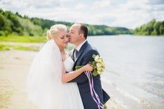 Sposa e sposo che camminano sul fiume Immagini Stock