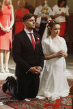 Sposa e sposo che pregano alla cerimonia di nozze in chiesa, bella Immagine Stock
