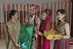 Sposa e sposo che ricevono i regali dai parenti. Immagini Stock