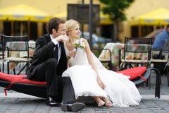 Sposa e sposo che si siedono dentro su una filiale Immagini Stock