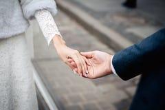 Sposa e sposo che si tengono per mano all'aperto Fotografia Stock Libera da Diritti