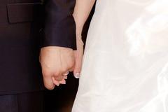 Sposa e sposo che si tengono per mano durante la cerimonia di nozze Fotografie Stock Libere da Diritti