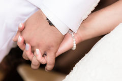 Sposa e sposo che si tengono per mano durante la cerimonia di nozze Fotografia Stock