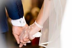 Sposa e sposo che si tengono per mano durante la cerimonia di nozze Immagine Stock