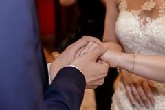 Sposa e sposo che si tengono per mano durante la cerimonia di nozze Immagini Stock