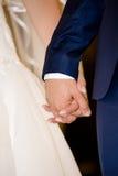 Sposa e sposo che si tengono per mano durante la cerimonia di nozze Fotografie Stock