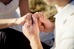 Sposa e sposo che si tengono per mano morbidamente vicino su honeymoon Immagine Stock