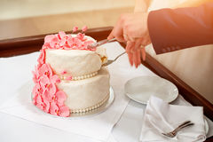 Sposa e sposo che tagliano la loro torta nunziale decorata con le orchidee Immagine Stock Libera da Diritti