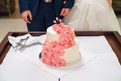 Sposa e sposo che tagliano la loro torta nunziale decorata con le orchidee Fotografia Stock Libera da Diritti