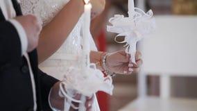Sposa e sposo che tengono le candele in chiesa alla cerimonia video d archivio