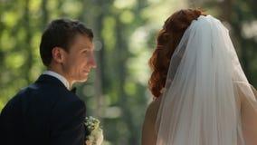 Sposa e sposo che vanno al vicolo del parco che parla l'un l'altro video d archivio