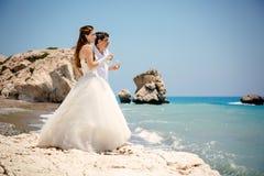 Sposa e sposo con i vetri di champagne sul mar Mediterraneo della spiaggia Fotografie Stock