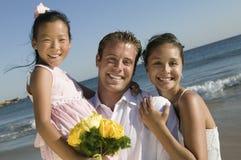 Sposa e sposo con la ragazza di fiore alla spiaggia immagini stock libere da diritti