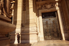 Sposa e sposo davanti ad una grande costruzione Fotografie Stock Libere da Diritti