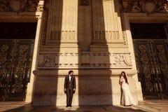 Sposa e sposo davanti ad una grande costruzione Immagini Stock Libere da Diritti