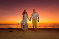 Sposa e sposo divertendosi su una spiaggia tropicale con il tramonto i Immagini Stock