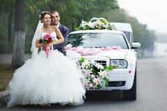 Sposa e sposo felici con il lmo Immagine Stock