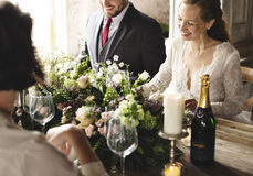 Sposa e sposo Having Meal con gli amici al ricevimento nuziale Fotografia Stock