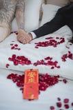 Sposa e sposo su un letto nel giorno delle nozze, cultura asiatica Fotografia Stock
