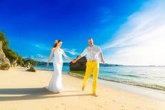Sposa e sposo su una spiaggia tropicale con il tramonto nel backg Immagini Stock