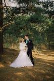 Sposa e sposo in un baciare della sosta le persone appena sposate sposa e sposo delle coppie alle nozze nella foresta di verde de Fotografie Stock