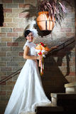 Sposa elegante con il mazzo di cerimonia nuziale sopra il muro di mattoni Fotografia Stock Libera da Diritti