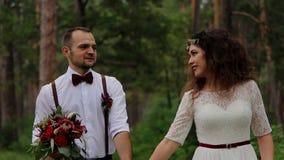 Sposa felice che è condotta dalla mano di un corteggiatore affascinante Lo guarda nell'occhio risata Lo sposo che tiene un bello  video d archivio