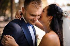 Sposa felice che abbraccia e che bacia il suo sposo sorridente immagine stock libera da diritti