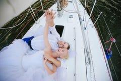 Sposa felice e sposo che abbracciano su un yacht Fotografia Stock Libera da Diritti