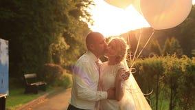 Sposa felice e sposo che camminano insieme e che baciano nel parco verde di autunno che giudica i palloni bianchi disponibili Tra archivi video