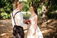 Sposa felice e sposo dei pantaloni a vita bassa che camminano nella foresta immagini stock libere da diritti