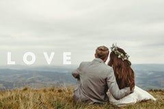 Sposa felice e sposo splendidi che si siedono sopra una montagna, per immagine stock libera da diritti