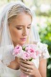 Sposa felice in un velo che la odora mazzo rosa Fotografie Stock