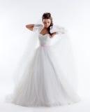 Sposa graziosa che posa in vestito alla moda con il velo immagine stock