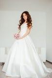Sposa Il giovane modello di moda con pelle perfetta e compone, fondo bianco, i capelli ricci, fiori Fotografia Stock
