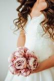 Sposa Il giovane modello di moda con pelle perfetta e compone, fondo bianco, i capelli ricci, fiori Fotografie Stock