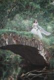 Sposa morta terrificante sul ponte contro i blocchi Halloween completo ha frequentato la scena della zucca della luna della casa fotografia stock