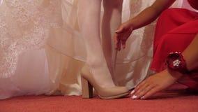 Sposa in scarpe a tacco alto bianche delle scarpe di vestito Primo piano Scarpe d'uso della donna stock footage