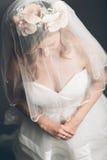Sposa schiva con il suo velo sopra il suo fronte Immagine Stock