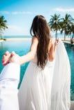 Sposa sexy nello sposo bianco della tenuta del vestito nella località di soggiorno di lusso Uomo principale della donna romantica Immagine Stock