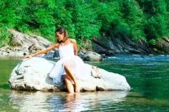 Sposa sola in una roccia dal fiume fotografie stock libere da diritti