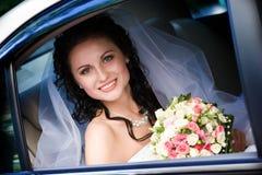 Sposa sorridente che si siede nell'automobile fotografia stock